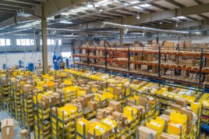 Warehouse with boxes on shelves and yellow containers holding shipping information and products